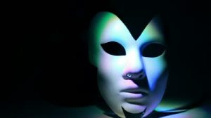stock-footage-pair-theatrical-masks-black-and-white-lit-by-color-light-at-dark-background